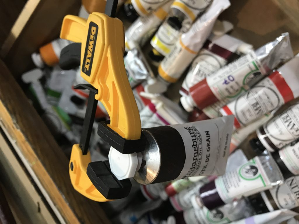 Clamp removing paint tube cap